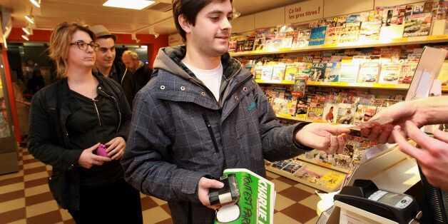 A man buys a copy of Charlie Hebdo newspaper at a newsstand in Saint Jean de Luz, southwestern France,...