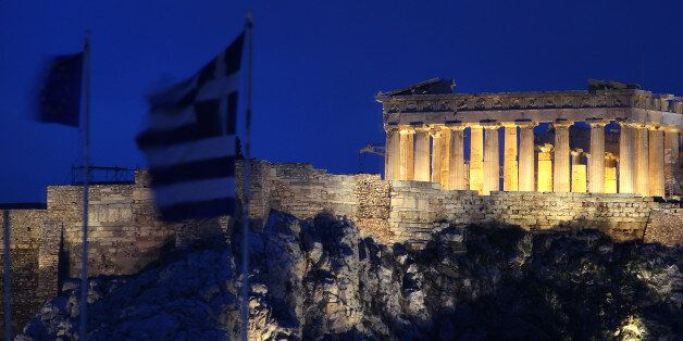 The flags of Greece, 2nd left, and European Union flutter from the roof of the Finance Minister at Athens'...