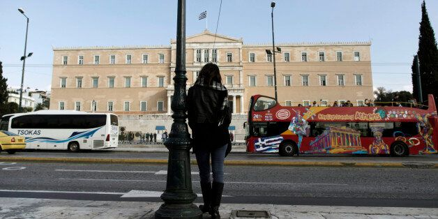 A woman stands opposite the Parliament in central Athens, Tuesday, Nov. 27, 2012. Greece has avoided...
