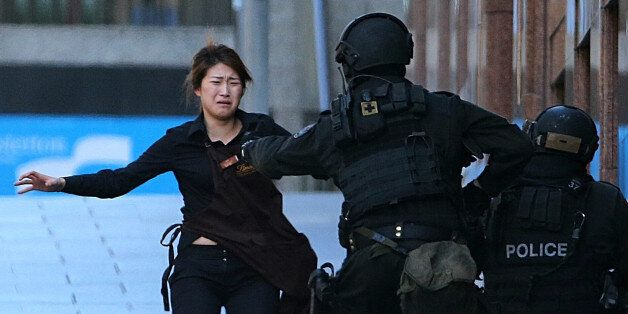 A hostage runs to armed tactical response police officers for safety after she escaped from a cafe under...