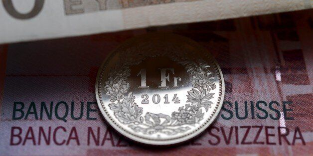 A Swiss coin is seen beneath a euro banknote on Januay 15, 2015 in Lausanne. In a shock announcement...