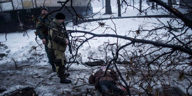 Separatist rebels look at the body of a man killed near a bus stop that was hit by Ukrainian army shells...