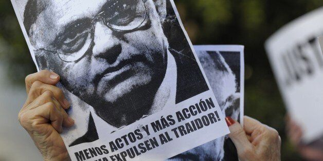 Women hold placards with the picture of Argentinian Foreign Minister Hector Timerman that read 'Less...