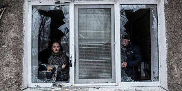 A Ukrainian woman looks through a broken window at their flat after it was hit by Ukrainian Artillery...