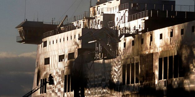 A fireman works outside the Norman Atlantic ferry after that has been towed into the port of Brindisi,...