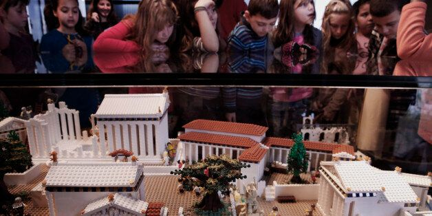 Schoolchildren look at a Lego model of the Acropolis in the new Acropolis Museum under the ancient citadel...