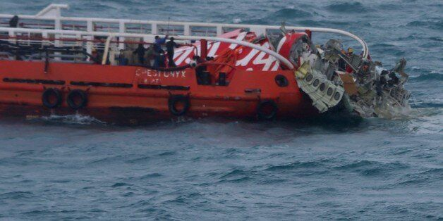 Members of an Indonesian search and rescue team pull wreckage from AirAsia flight QZ8501 onto the Crest...