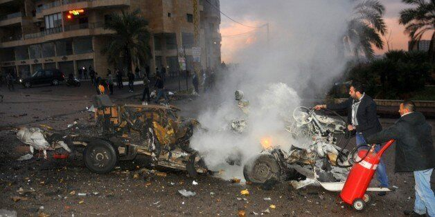 Lebanese extinguish a minibus in fire at the site of an explosion on February 3, 2014 in Choueifat, south...