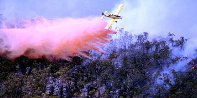 In this Thursday, Jan. 16, 2014 photo released by Victoria Country Fire Authority, a water bomber works...