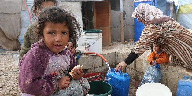 A Syrian girl eats a sandwich as others fill water containers at a refugee camp in Deir Zannoun village,...