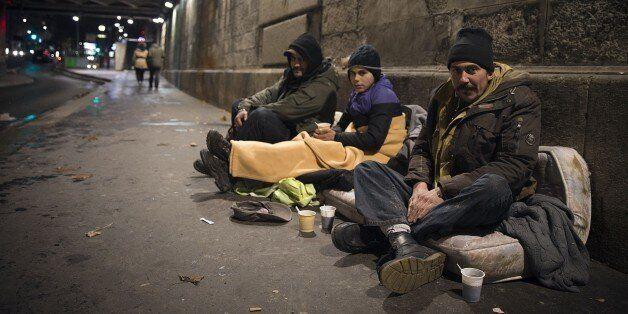 Romanian homeless people take shelter under a bridge in Paris, on December 13, 2014. AFP PHOTO / JOEL...