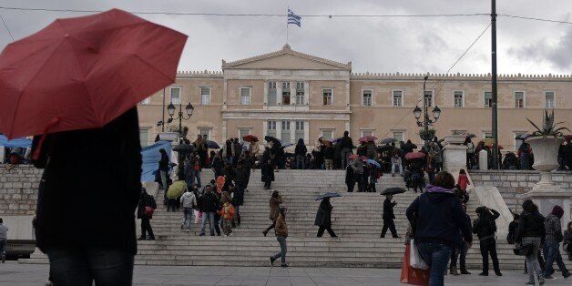 People walk in front of the Greek parliament on December 10, 2014. The Greek government unexpectedly...