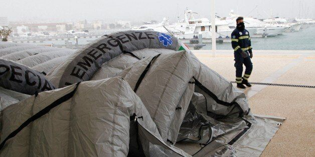 An Italian Red Cross volunteer walks past a tent being set up to accommodate some of the rescued passengers...