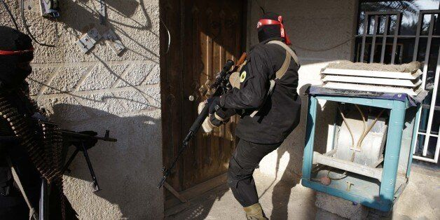 Pro-Iraqi government fighters, some belonging to the Iraqi Imam Ali Brigade, inspect houses during an...