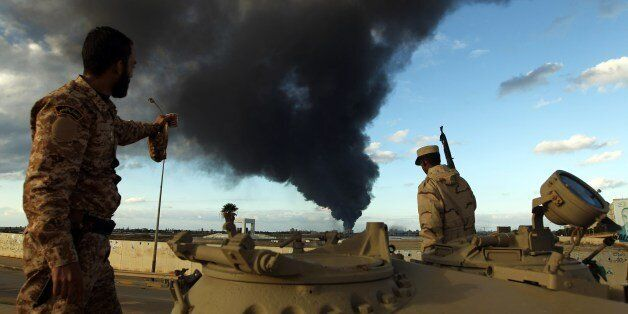 Members of the Libyan army stand on a tank as heavy black smoke rises from the city's port in the background...