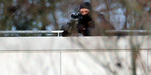 A hooded police officer aim from a rooftop in Dammartin-en-Goele, northeast of Paris, where the two brothers...