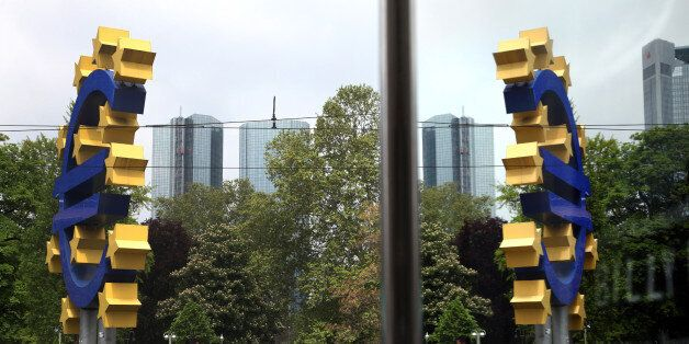 The euro sign sculpture is seen reflected in a window outside the European Central Bank (ECB) headquarters...