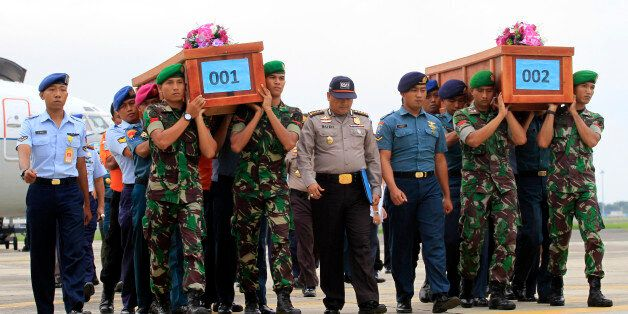 Indonesian soldiers carry the bodies of victims of AirAsia Flight 8501 upon arrival at Indonesian Military...