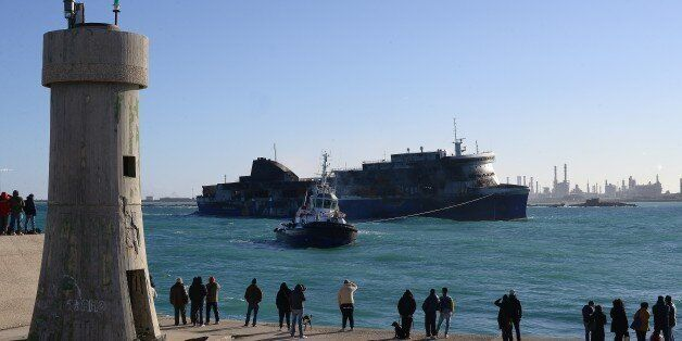 People look at the Italian-owned Norman Atlantic ferry arriving in the port of Brindisi on January 2,...