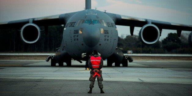 Airman 1st Class Damien Goodman marshals a C-17A Globemaster III before a flight Feb. 28, 2013, at Joint...