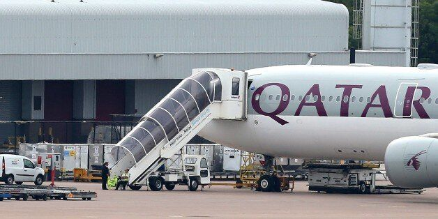 Airport personnel are seen at the foot of the stairs of the Qatar Airways plane that was forced to make...