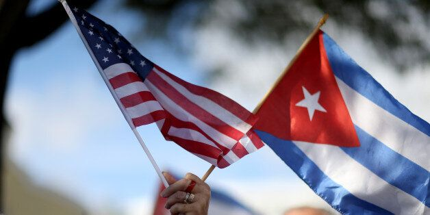 MIAMI, FL - DECEMBER 20: A protester holds an American flag and a Cuban one as she joins with others...