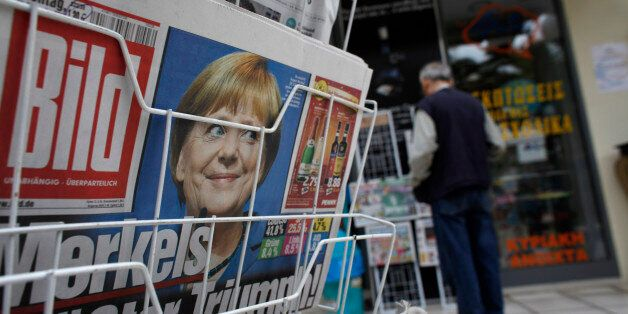 A photograph of Germany's Chancellor Angela Merkel looks out from the front page of Bild on a newspaper...