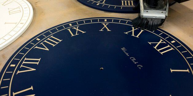 A computer numerical control (CNC) machine engraves numerals on personalized wall clock faces at the...