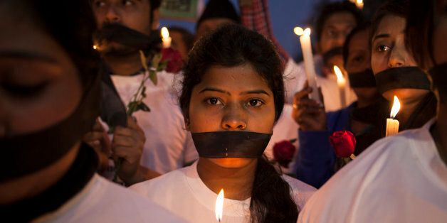 Indian women participate in a candle light vigil at a bus stop where the victim of a deadly gang rape...