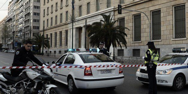 Policemen stand guard in front of Bank of Greece headquarters after a booby-trapped car exploded nearby,...