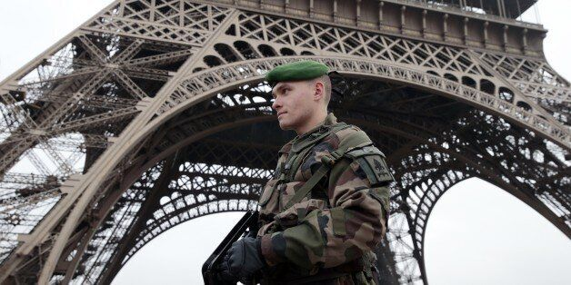 A French soldier patrols in front of the Eiffel Tower on January 7, 2015 in Paris as the capital was...