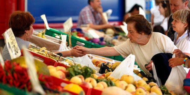 A customer, right, pays for her goods in euros at a fruit and vegetable stall in an outdoor market at...