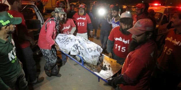 Pakistani rescue workers carry the lifeless body of a bus accident victim to a hospital in Karachi, Pakistan,...