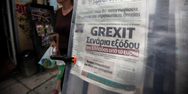 A pedestrian passes a 'Grexit' headline on a newspaper displayed at a street kiosk in Athens, Greece,...