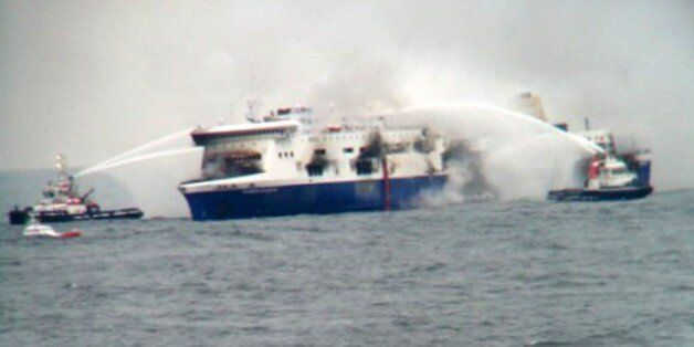 In this photo taken from a nearby ship, vessels try to extinguish the fire at the Italian-flagged Norman...