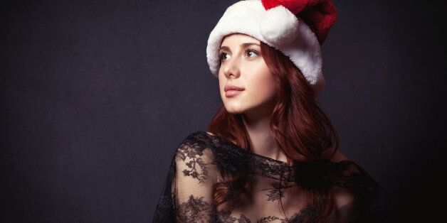Portrait of a beautiful woman in style dress and Santa Claus hat on dark