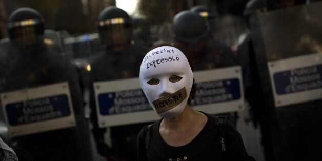A woman wearing a mask stands in front of riot police officers cordon off the area during a protest against...