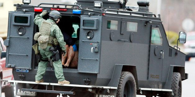 Police move with a person in the back of a police vehicle near the scene of a shooting Monday, Dec. 15,...