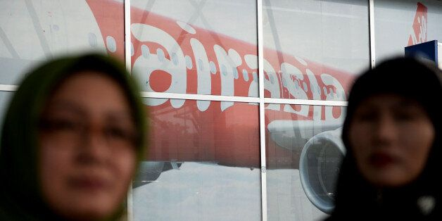 Travelers stand in front of an advertisement for AirAsia Bhd. in a departure hall at Soekarno-Hatta International...