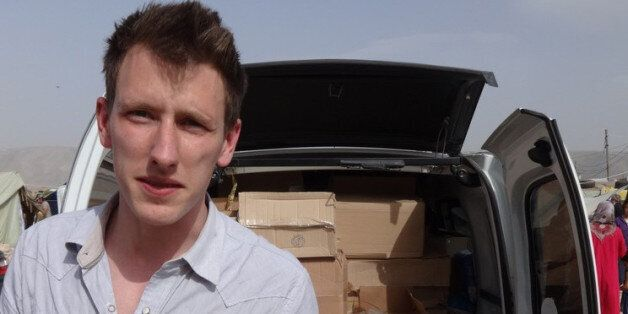 This undated photo provided by Kassig Family shows Peter Kassig standing in front of a truck filled with...