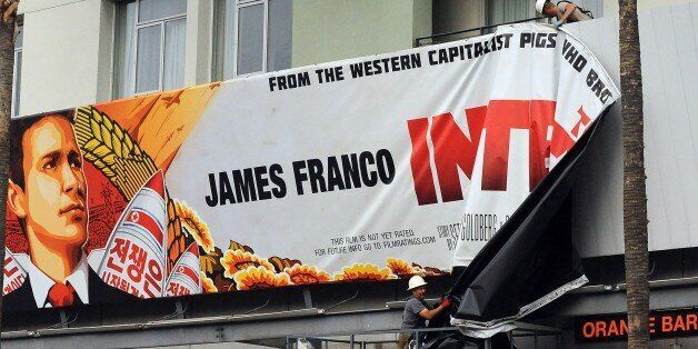 Workers remove a poster for 'The Interview' from a billboard in Hollywood, California, December 18, 2014...