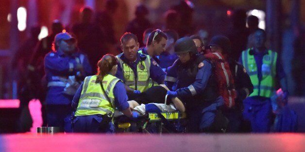 An injured hostage is carried out of a cafe in the central business district of Sydney on December 16,...