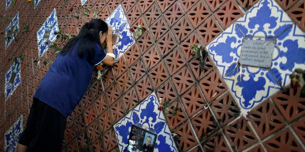 A woman offers prayers on a tiled memorial wall displaying names of victims from the Asian tsunami, Friday,...