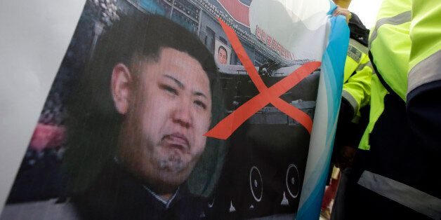 Activists who plan to send anti-North Korea leaflets, hold a defaced image of North Korean leader Kim...
