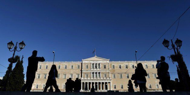People walk past the Greek parliament in Athens on December 17, 2014. Greece stood a step away from early...