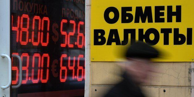 A pedestrian walks past a board listing foreign currency rates against the Russian ruble outside an exchange...