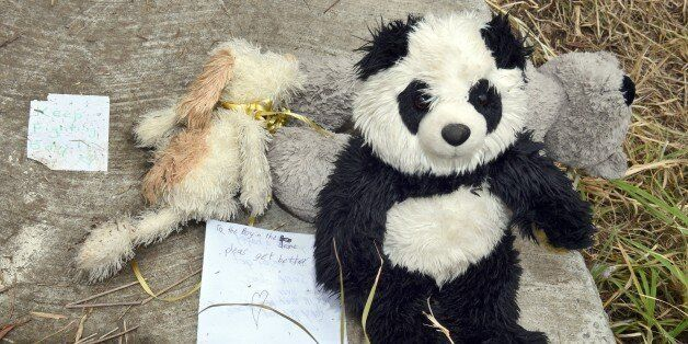 Teddy bears and notes of support are displayed on the cover of a 2.5-metre-deep (8.2-feet) deep drain...