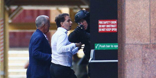 SYDNEY, AUSTRALIA - DECEMBER 15: A hostage is seen outside the Lindt Cafe, Martin Place on December 15,...