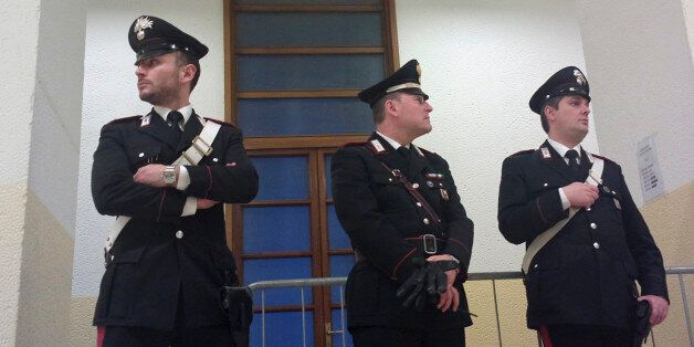 Carabinieri policemen stand in a corridor of the court in Milan, Italy, Thursday, April 10, 2014. A Milan...