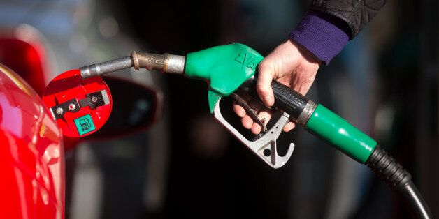 A driver holds a fuel nozzle as he prepares to refuel his luxury Ferrari automobile with unleaded petrol...